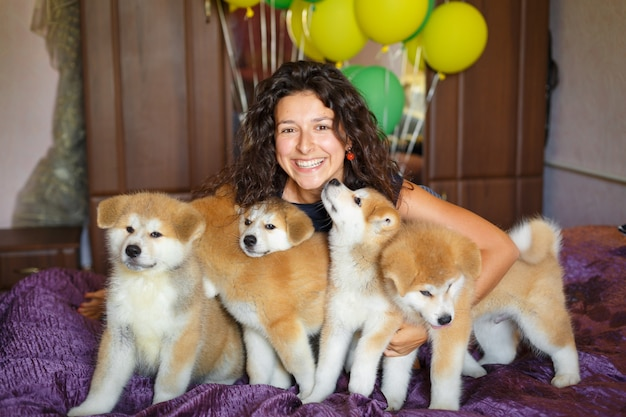 Handsome brunette girl have fun hugs and play with akita inu puppies