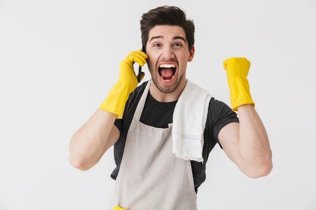 흰색 위에 고립 된 앞치마를 입고 잘 생긴 갈색 머리 집주인, 휴대 전화에 대 한 얘기