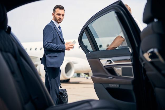 上品なスーツを着たハンサムなブルネットの男がタクシーのそばに立っている彼のキャリーオンを保持しています