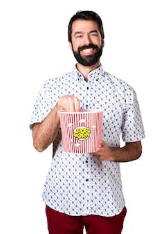 Bel uomo brunetta con la barba che mangia popcorn