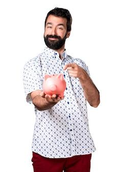 Красивый брюнетка с бородой, холдинг piggybank