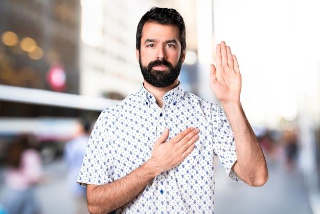 Handsome brunette man with beard making an oath