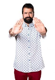 Красивый брюнетка человек с бородой делает знак остановки
