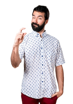 Красивый брюнетка с бородой, делая маленький знак