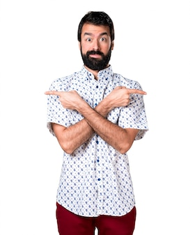 Handsome brunette man with beard pointing to the laterals having doubts