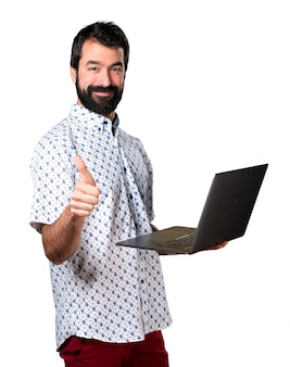 Handsome brunette man with beard with laptop