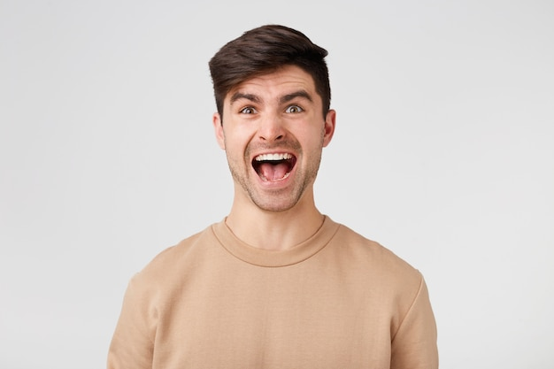 Uomo bello del brunette con la bocca aperta