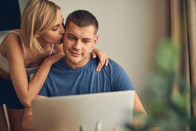 금발 슬림 여자가 포옹하고 그에게 키스하는 동안 컴퓨터에서 온라인으로 작업하는 잘 생긴 갈색 머리 남자