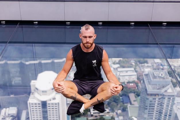 Handsome brutal bearded caucasian man on rd glass floor in bangkok