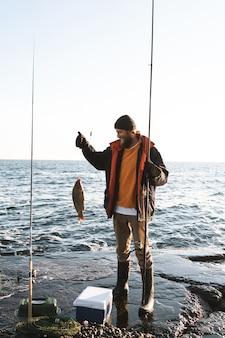 ハンサムな残忍なひげを生やした漁師が海岸で釣り竿と一緒に立っているコートを着て、釣った魚を見せています