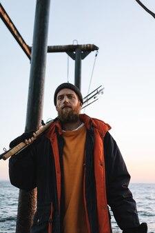 海岸で釣り竿と立っているコートを着ているハンサムな残忍なひげを生やした漁師