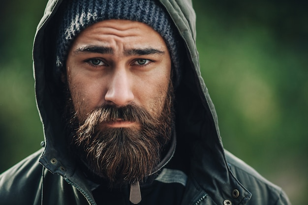 Handsome brutal bearded man with dark beard and mustache dressed in winter clothes