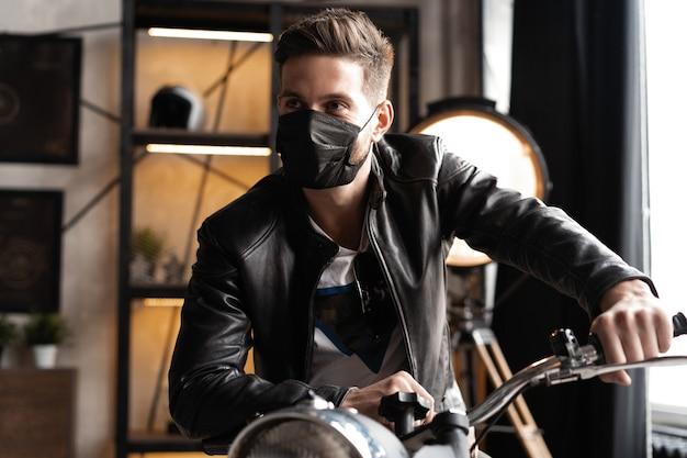楽しみにしてオートバイに座っている革のジャケットの黒いマスクのハンサムな残忍な男性バイカー
