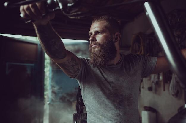 Красивый брутальный мужчина с бородой сидит на мотоцикле в своем гараже и смотрит в сторону