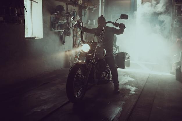 Красивый брутальный мужчина с бородой сидит на мотоцикле в своем гараже