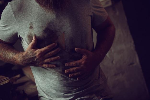 Красивый брутальный мужчина с бородой стоит в своем гараже на фоне инструментов ремонта и вытирает руки о рубашку