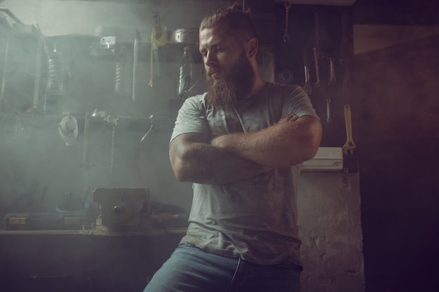 Handsome brutal man with a beard standing in his garage against the background of repair tools