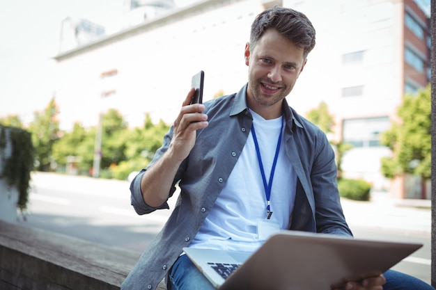 Handsome business executive holding mobile phone and laptop