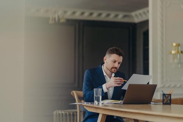 Красивый бизнес-руководитель в темно-синем костюме сидит за своим рабочим столом в светлом офисе, работая над данными, представленными на листе формата а4, с карандашом в руке, при этом серьезный и сосредоточенный