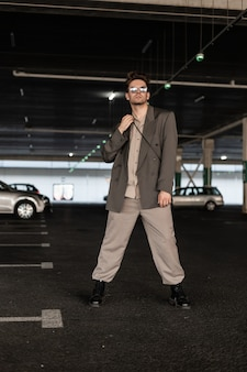 ブーツとファッショナブルな衣装でサングラスをかけたハンサムなビジネス男性モデルが駐車場に立っています