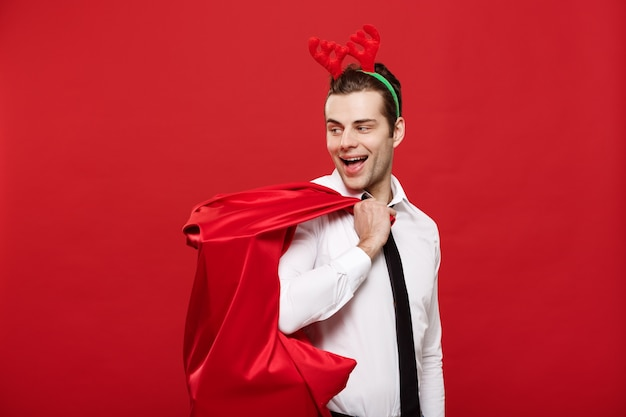 Handsome business man celebrate merry christmas and happy new year wear reindeer hairband holding santa red big bag.