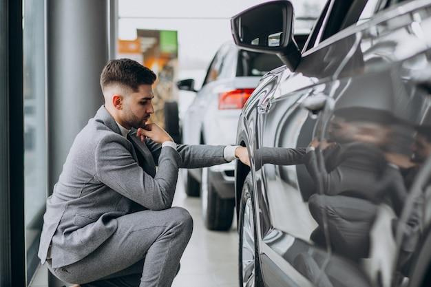 잘 생긴 사업가 자동차 쇼룸에서 자동차를 선택
