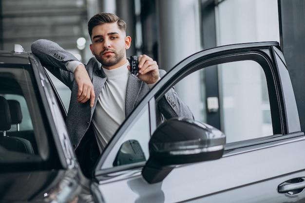 Красивый деловой человек, выбирая автомобиль в автосалоне