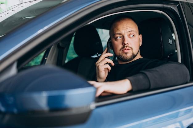 車のショールームで車を選ぶハンサムなビジネスマン