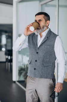 Handsome business man drinking coffee in office