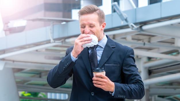 ハンサムなビジネスの男性が屋外で朝食のファーストフードのハンバーガーを食べて、スマート布スイートで一杯のコーヒーを飲みます。