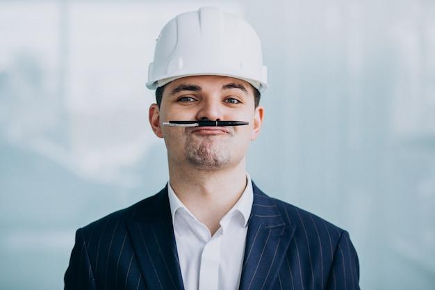 建物のヘルメットでハンサムなビジネス人エンジニア