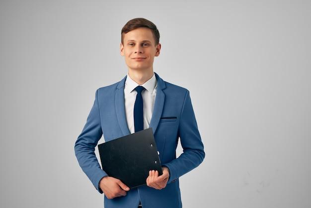 スタジオマネージャーの手にドキュメントとスーツを着たハンサムなビジネスマン。高品質の写真
