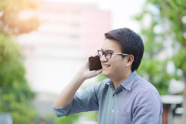 모바일 스마트 휴대 전화를 사용 하여 다행에 잘 생긴 비즈니스 사람. 아시아 남자
