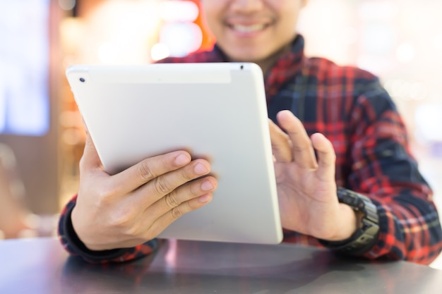 커피 숍에서 기쁜 사용 태블릿에 잘 생긴 비즈니스 사람. 아시아 남자