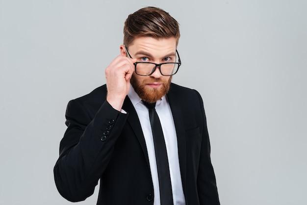 그의 안경 너머로 보이는 검은 양복에 잘생긴 사업가. 격리 된 회색 배경