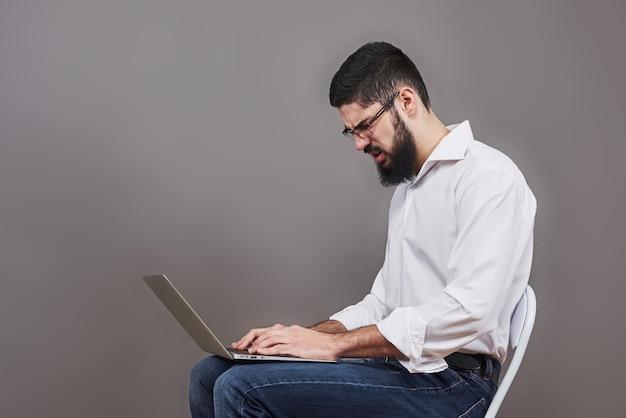 안경에 노트북을 손에 들고 뭔가 쓰는 양복 잘 생긴 비즈니스 사람. 측면보기. 격리 된 회색 배경입니다.