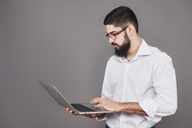 안경 및 소송 손에 노트북을 들고 뭔가 쓰는 잘 생긴 사업가.