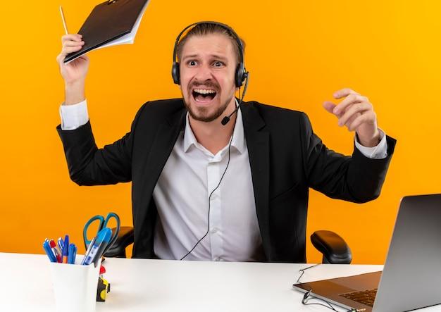 오렌지 배경 위에 offise에서 테이블에 앉아 공격적인 표정으로 외치는 제쳐두고 클립 보드를 들고 마이크와 양복과 헤드폰에서 잘 생긴 비즈니스 남자