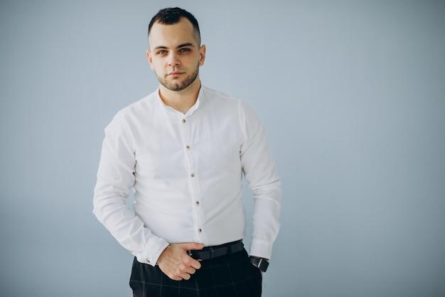 オフィスで分離された白いシャツを着たハンサムなビジネスマン