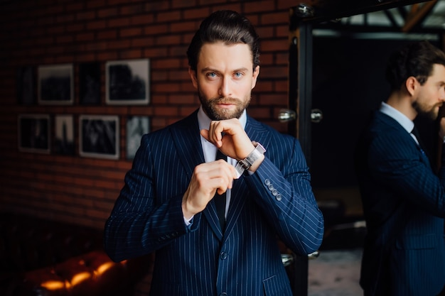 A handsome business man looking at camera with watch on his hand.