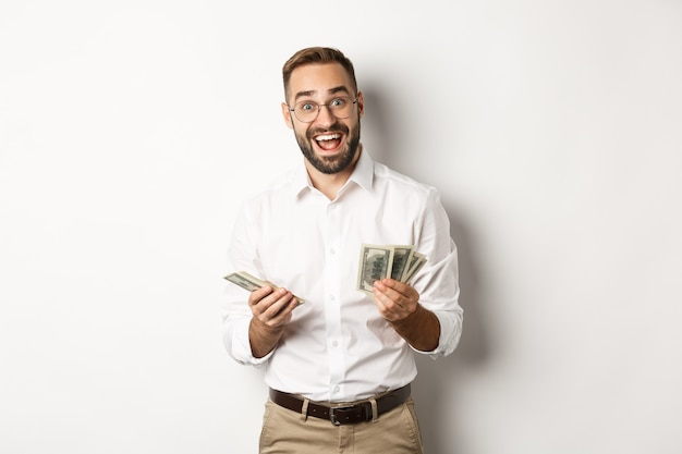 Handsome business man looking excited while counting money, standing over white background.