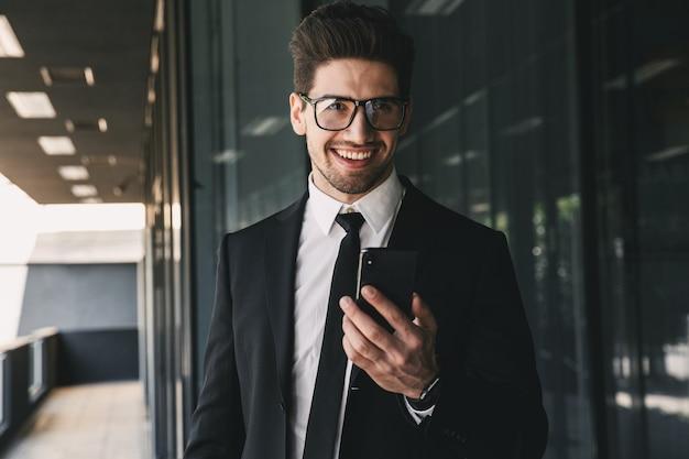 携帯電話を使用してビジネスセンターの近くのハンサムなビジネスマン。