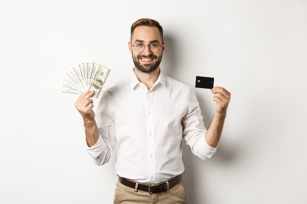 Handsome business man showing credit card and money dollars, smiling satisfied, standing over white background.
