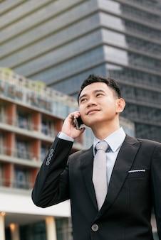 彼の会社のオフィスビルで携帯電話を話すハンサムなビジネスマン、モデルはアジア人男性です