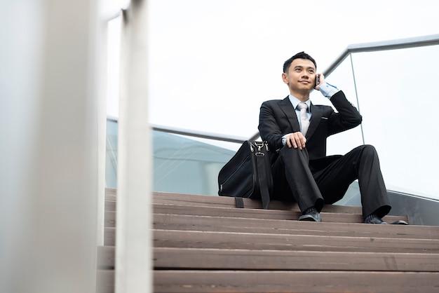 通りの階段に座って携帯電話を話すハンサムなビジネスマン、モデルはアジア人男性です