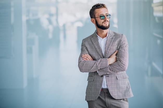 Bel uomo d'affari in piedi in ufficio