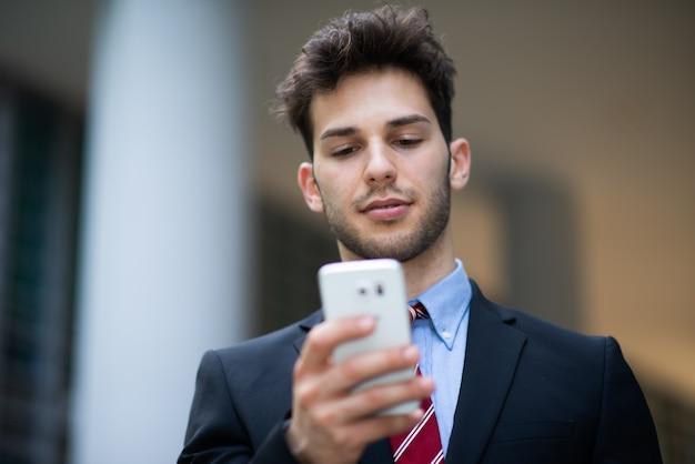 携帯電話を使用してハンサムなビジネスマン