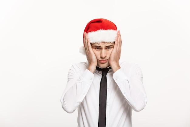 白でストレスの多い表情でポーズをとってサンタの帽子をかぶっているハンサムなビジネスマン。