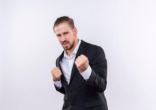 흰색 배경 위에 서있는 적극적인 표정으로 카메라를보고 주먹을 떨림 양복을 입고 잘 생긴 비즈니스 남자