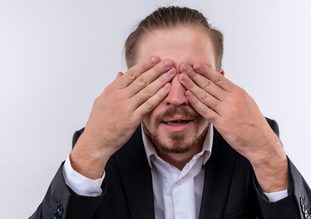 흰색 배경 위에 서있는 팔으로 눈을 덮고 양복을 입고 잘 생긴 비즈니스 남자